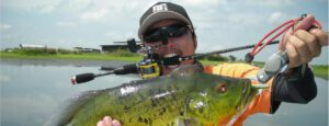 best baitcaster for kayak - man using baitcaster to catch fish