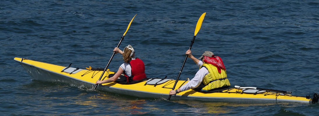 Stay Safe When Fishing On A Kayak - two people with hats and PFDs