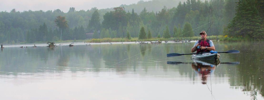 high end spinning reels kayaks - man fishing in sit in kayak