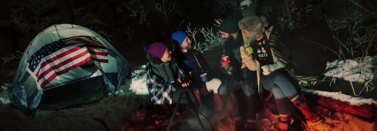 tips for winter camping - sitting around campfire